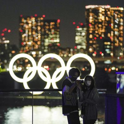 Nuoret valokuvaavat itseään iltavalossa olympiarenkaiden edessä Tokiossa.