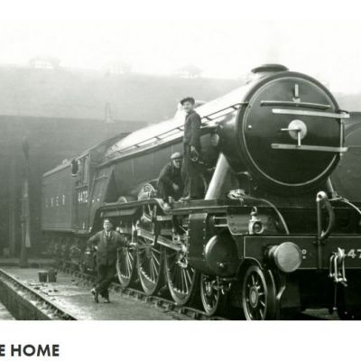 Mustavalkoinen kuva höyryveturista miehistöineen tallin edessä.