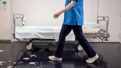 En sjukskötare går förbi en tom sjukhussäng.