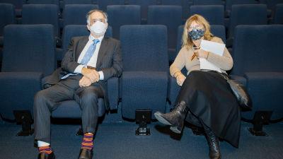 Francis Ford Coppola och Annika Hällsten sitter i en biosalong. Båda har ansiktskydd på sig och sitter några bänkar isär från varandra.