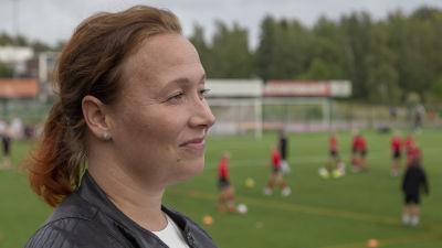 Jalkapalloa harrastavan pojan äiti Helena Sarso sivuprofiilikuvassa, kuvattu Espoonlahden urheilupuistossa.