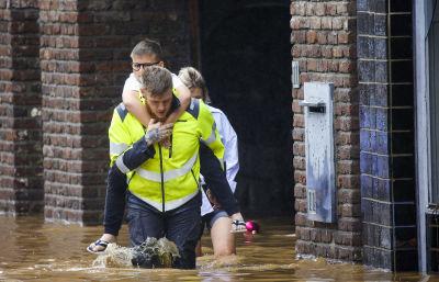 En man bär en pojke på sin rygg genom översvämningar i Belgien.