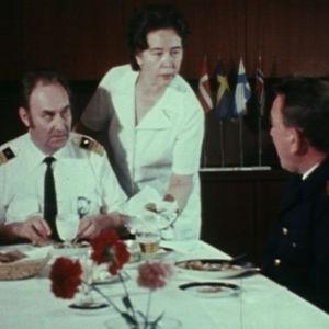 Henkilökunta tarjoilee kapteenille ruokaa.