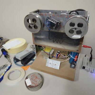 Kaksikelainen laatikko, johtoja ja pattereita työpöydällä.