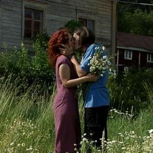 Hääpari suutelee niityllä.