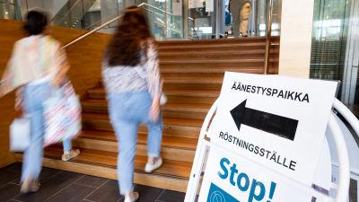 """Etualalla kyltti, jossa lukee """"äänestyspaikka"""" ja on nuoli. Takana kaksi naista kävelee nuolen osoittamaan suuntaan."""