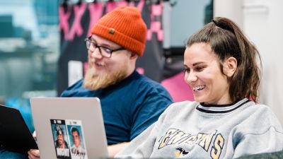 En man och en kvinna sitter på en soffa med två laptops i famnen.