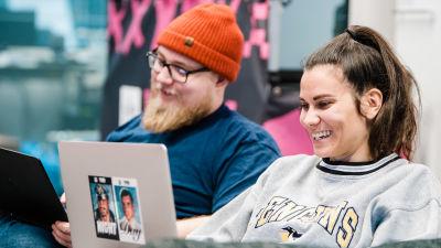 En ung kvinna och en ung man skrattar där de sitter brevid varandra med sina bärbara datorer.
