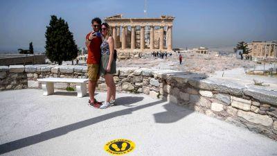Ett par tog en selfie framför Parthenon-templet på Akropolis-klippan den 18 maj. På grund av coronakrisen finns märken på klippan som ska underlätta social distansering.
