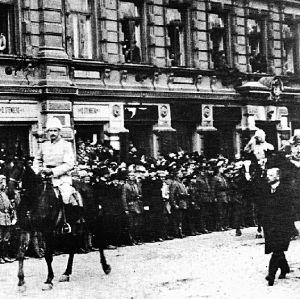Mannerheim rider på en häst i en stad.