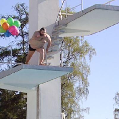 Mies hyppää uimastadionin hyppytornista.