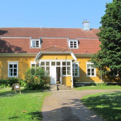 Keltainen, punakattoinen rakennus kulttuuripappila Sylvi.