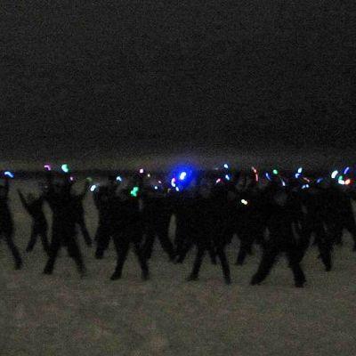 Tummia hahmoja Näsijärven jäällä valot käsissään