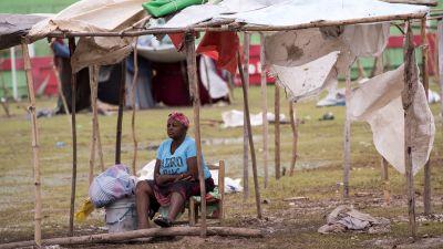 Bild på kvinna som bygger ett tält som ska skydda henne mot regnet.