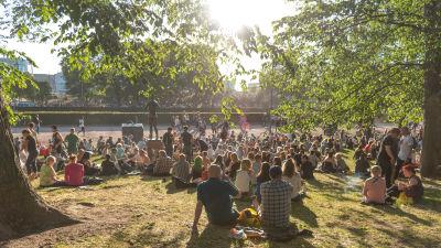 Människor sitter i en fullsatt park.