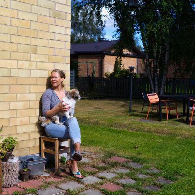 Terhi Vallineva istuu asuntonsa takapihalla puutarhatuolissa. Aurinko paistaa ja Vallineva pitää sylissään Börje-koiraa.