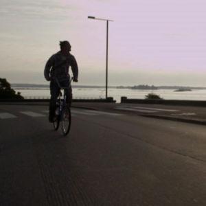 Mies pyöräilee auringon paistaessa takaa
