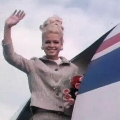Leena Brusiin vilkuttaa lentokoneen ovella