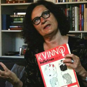 Professor Ebba Witt-Brattström visar ett exemplar av Kvinnobulletinen.