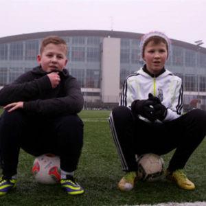 Pojat istuvat jalkapallojen päällä