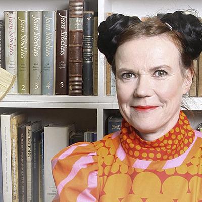 Rosa Liksom kirjahyllyn edessä