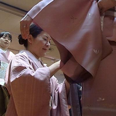 Naista autetaan pukeutumaan kimonoon