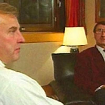 två män sitter i ett rum