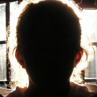 En siluett av ett barnansikte i motljus.