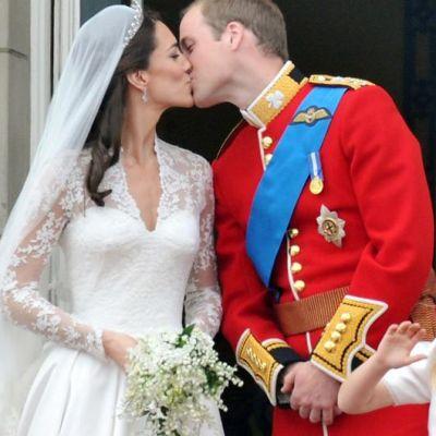 Vastavihityt herttuatar Catherine ja prinssi William suutelevat Buckinghamin palatsin parvekkeella.