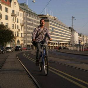 Mies ajaa pyörällä Kauppatorilta