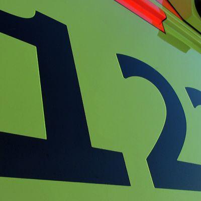 Hätänumero 112 auton kyljessä.