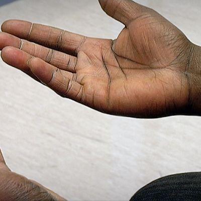 Tummaihoisen miehen kädet