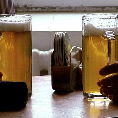 Kaksi henkilöä pitelee oluttuoppeja.