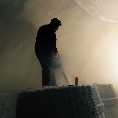 Työmies viimeistelee moottorisahalla lumilinnan veistosta