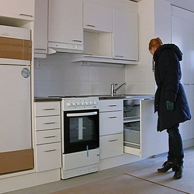 Nainen tutkii keittiötä asuntoesittelyssä