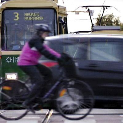 Raitiovaunut 3 ja 2 odottavat matkustajia Eläintarhan pysäkillä. Niiden edestä ylittävät kadun tumma henkilöauto ja pyöräilijä.