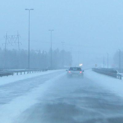 Auto ajaa lumisateessa ja tuulessa.