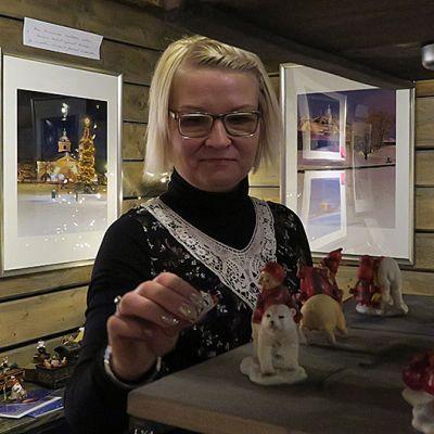 Nainen laittaa joulukoristeita hyllylle.