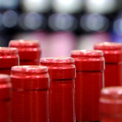 Punaviinipulloja jonossa ja rivissä kaupan hyllyllä.