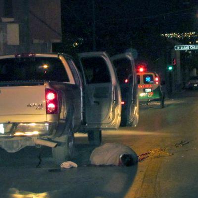 öinen katu jolla seisoo auto ovet auki ja sen vieressä kadulla makaa ruumis
