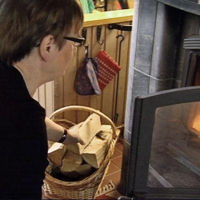 Nainen laittaa puita takkaan.