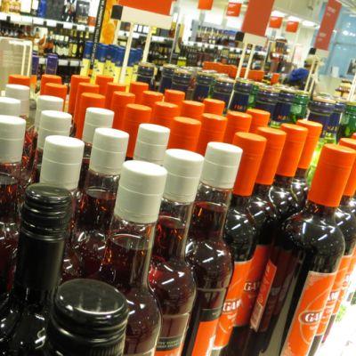Alkoholijuomapakkauksia Alkon hyllyssä.
