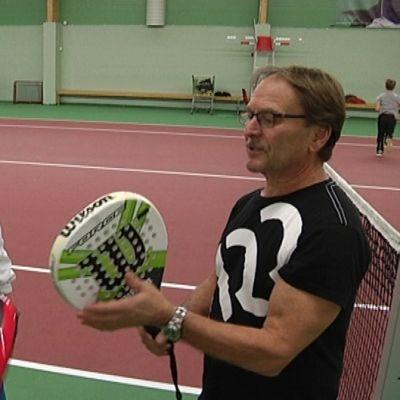 Kaksi miestä tutkimassa padel-tennismailoja.