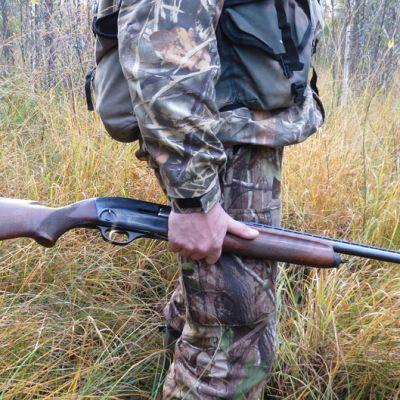 Metsästäjä ase kädessä.