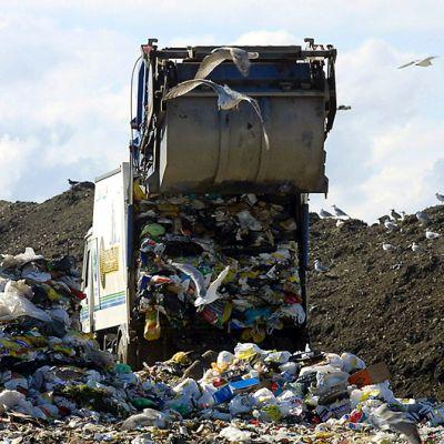 Jäteauto tuomassa lastia kaatopaikalle.
