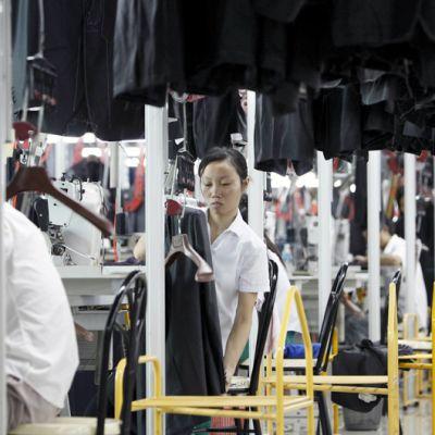 Kiinalaiset ompelijat työskentelevät vaatetehtaan liukuhihnalla.