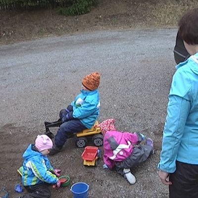 Perhepäivähoitaja katselee, kun neljä hoitolasta leikkii pihalla.