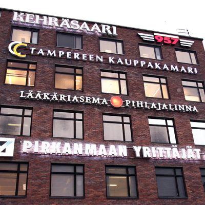 Rakennus Kehräsaaressa Tampereella. Talon seinässä useita valomainoksia.