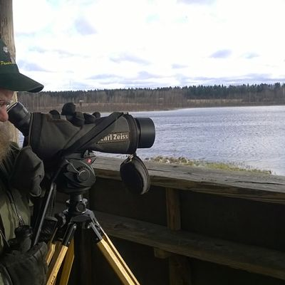 Mies tähyilee maisemaa kameralla.