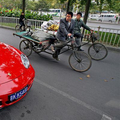 Kaksi polkupyöräilijää katsoo punaista urheiluautoa.
